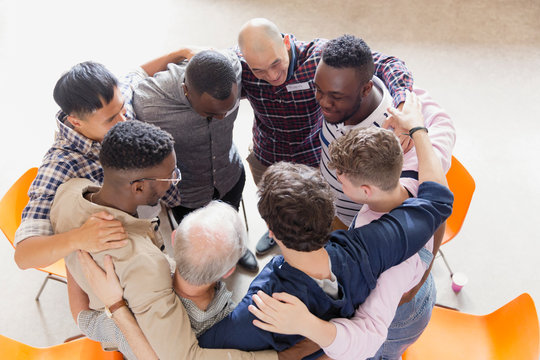 Men hugging in huddle in group therapy