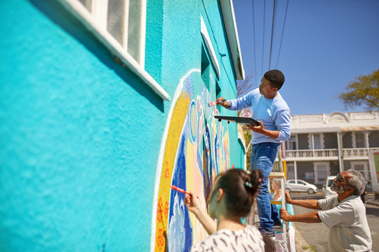 Community volunteers painting vibrant mural on sunny urban wall