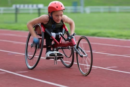 Determined, tough teenage girl paraplegic athlete speeding along sports track in wheelchair race