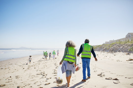 Volunteers cleaning up litter on sunny, sandy beach