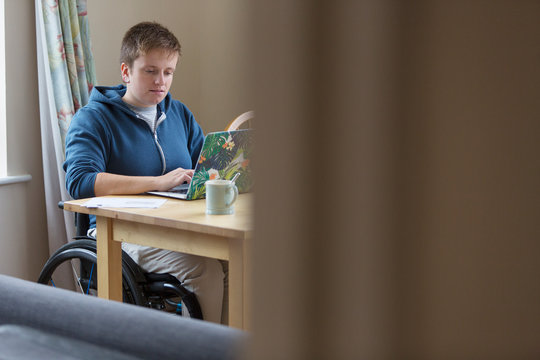 Young woman in wheelchair using laptop at dining table