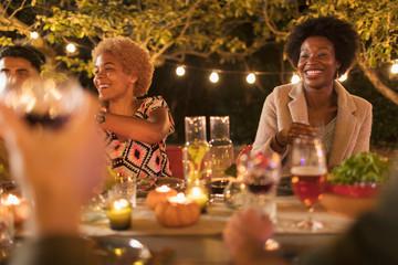 Happy friends enjoying dinner garden party