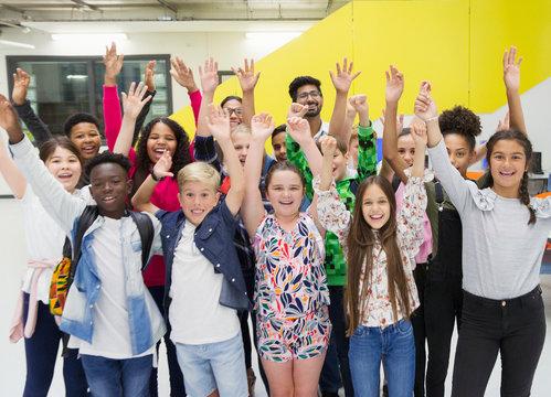 Portrait enthusiastic junior high students teachers cheering arms raised