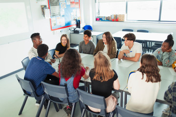 High school students talking in debate class at table in classroom