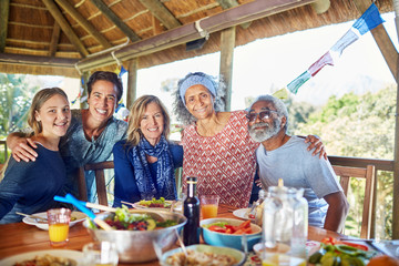 Portrait happy friends enjoying healthy meal in hut during yoga retreat