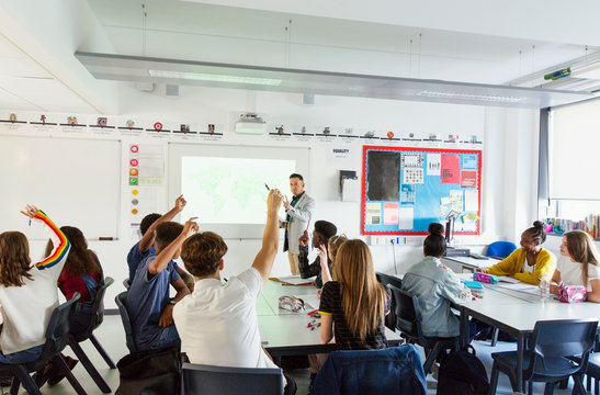 High school teacher calling on students with hands raised during lesson in classroom