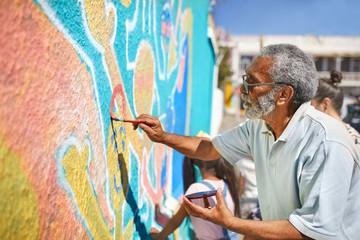 Senior male volunteer painting vibrant mural on sunny wall