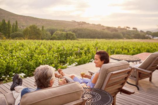 Couple relaxing, drinking wine on idyllic, rural resort patio