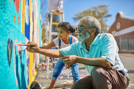 Grandfather granddaughter volunteers painting vibrant mural on sunny urban wall