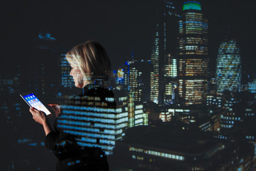 Double exposure businesswoman using digital tablet against highrise lights at night