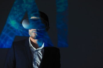 Double exposure businessman with virtual reality simulator glasses against AI text