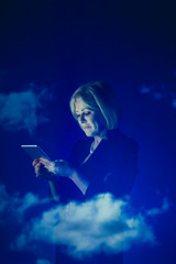 Double exposure businesswoman using digital tablet against blue sky with clouds