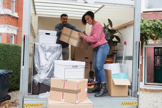 Couple unloading moving van outside new house