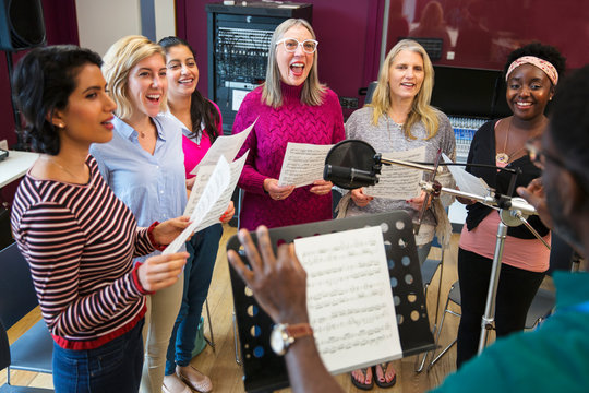 Male conductor leading womens choir sheet music singing in music recording studio