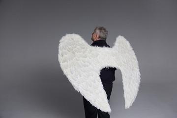 Serene man wearing angel wings, looking up