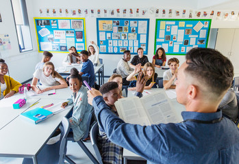 High school teacher calling on students during lesson in classroom