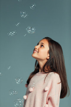 Happy, curious girl watching falling bubbles
