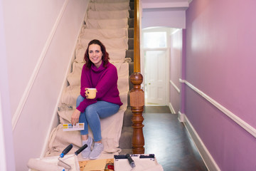 Portrait confident woman redecorating, looking at paint swatch on stairs