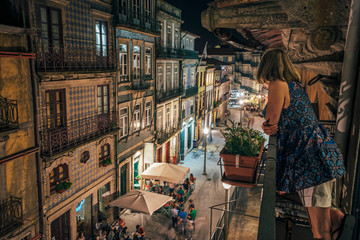 Woman standing on balcony, looking at ornate architecture, Porto, Portugal