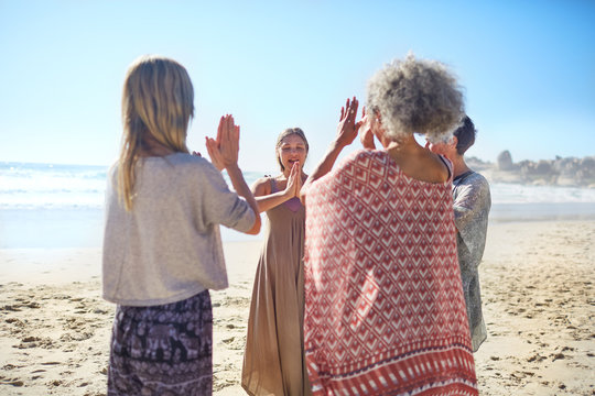 Women friends hands clasped in circle on sunny beach during yoga retreat