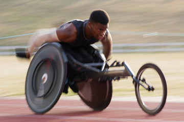 Determined young male paraplegic athlete speeding along sports track in wheelchair race Fotomurales