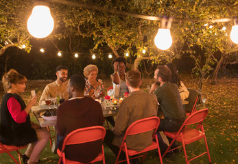 Friends enjoying dinner garden party under trees with fairy lights