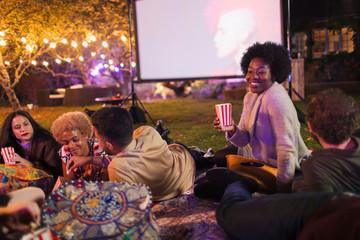 Friends eating popcorn, enjoying movie on projection screen in backyard