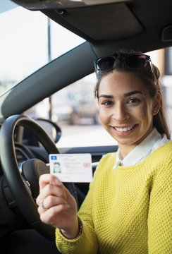 Portrait happy young woman holding new drivers license in car