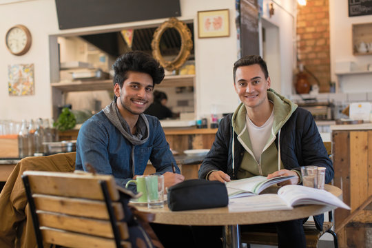Portrait confident young male college students studying at cafe table