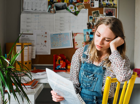 Focused young woman working in home office, reading paperwork