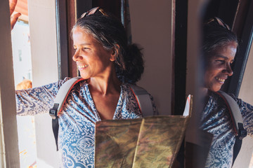 Smiling female tourist with map looking out sunny window