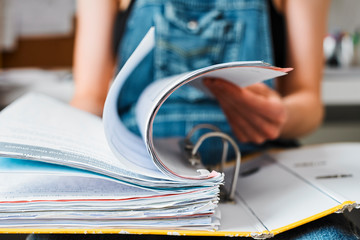 Female college student studying, looking through binder