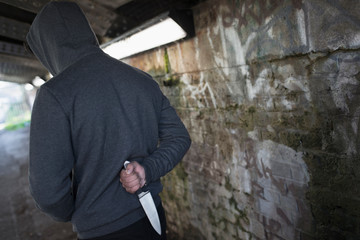 Dangerous man with knife behind back in urban tunnel
