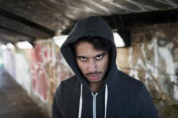 Portrait menacing young man in urban tunnel