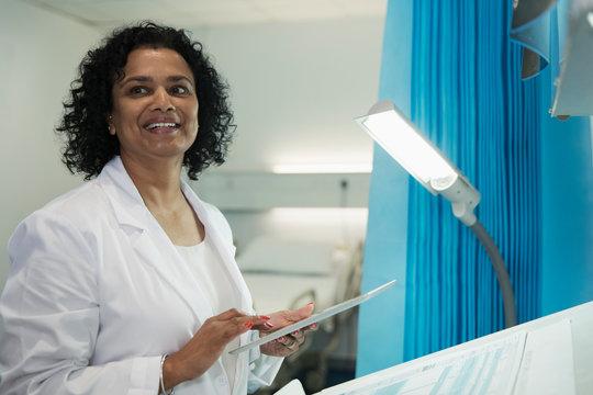 Smiling female doctor using digital tablet in hospital room