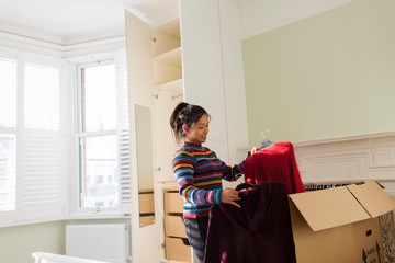 Woman unpacking clothing from moving box in bedroom