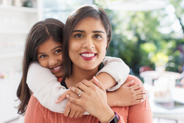 Portrait happy, affectionate mother and daughter hugging