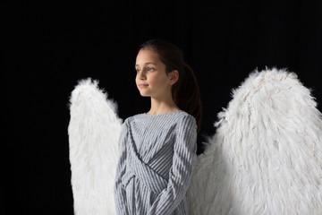 Serene girl wearing angel wings