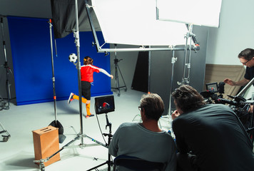 Photographers and teenage girl soccer player in studio photo shoot