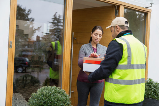 Woman signing for package from deliveryman at front door