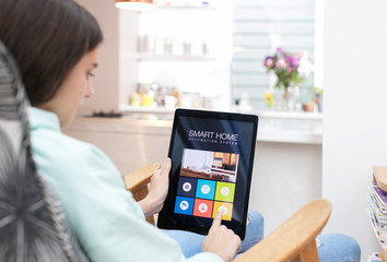 Girl using smart home automation system on digital tablet
