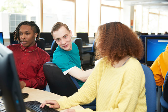 College students studying together at computers in library