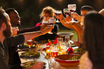 Friends toasting wine glasses at dinner garden party