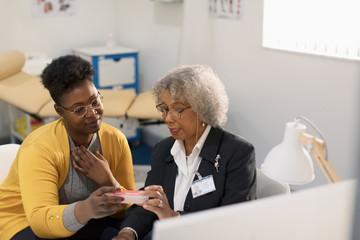 Female doctor prescribing medication to patient in doctors office