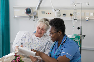 Female nurse discussing paperwork with senior patient in hospital room