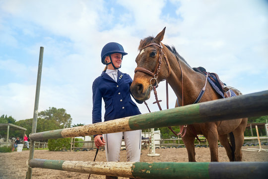 Teenage girl in equestrian helmet with horse at obstacle in paddock