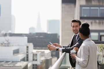Business people talking on sunny, urban balcony