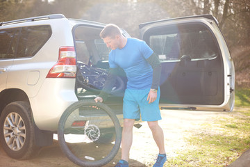 Male cyclist removing bike tire from back of SUV in sunny parking lot