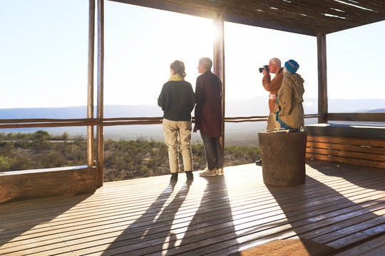 Friends looking at view from sunny safari lodge balcony