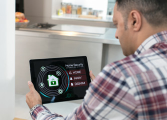Man setting smart home security alarm from digital tablet in kitchen